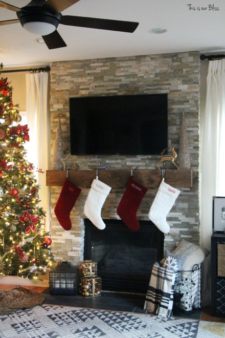 This is our Bliss family-room-tree-stockings-hung-on-mantle-stacked-stone-fireplace-floating-mantle-This-is-our-Bliss